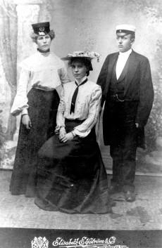 Agda Sjölin i Stockholms privata gymnasiums mössa, Axie Sjölin i hatt och Agdas latininformator Alfred Ströberg, 1907, nr 30